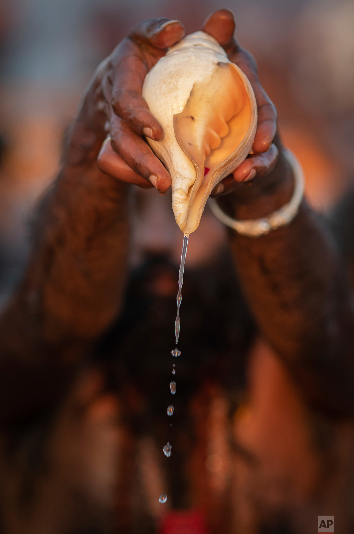 A sadhu, a Hindu holy man, pours water from a shell as he takes a ceremonial cleansing dip at Sangam, during the Kumbh Mela festival in Prayagraj, India on Jan. 15, 2019. (AP Photo/Bernat Armangue)