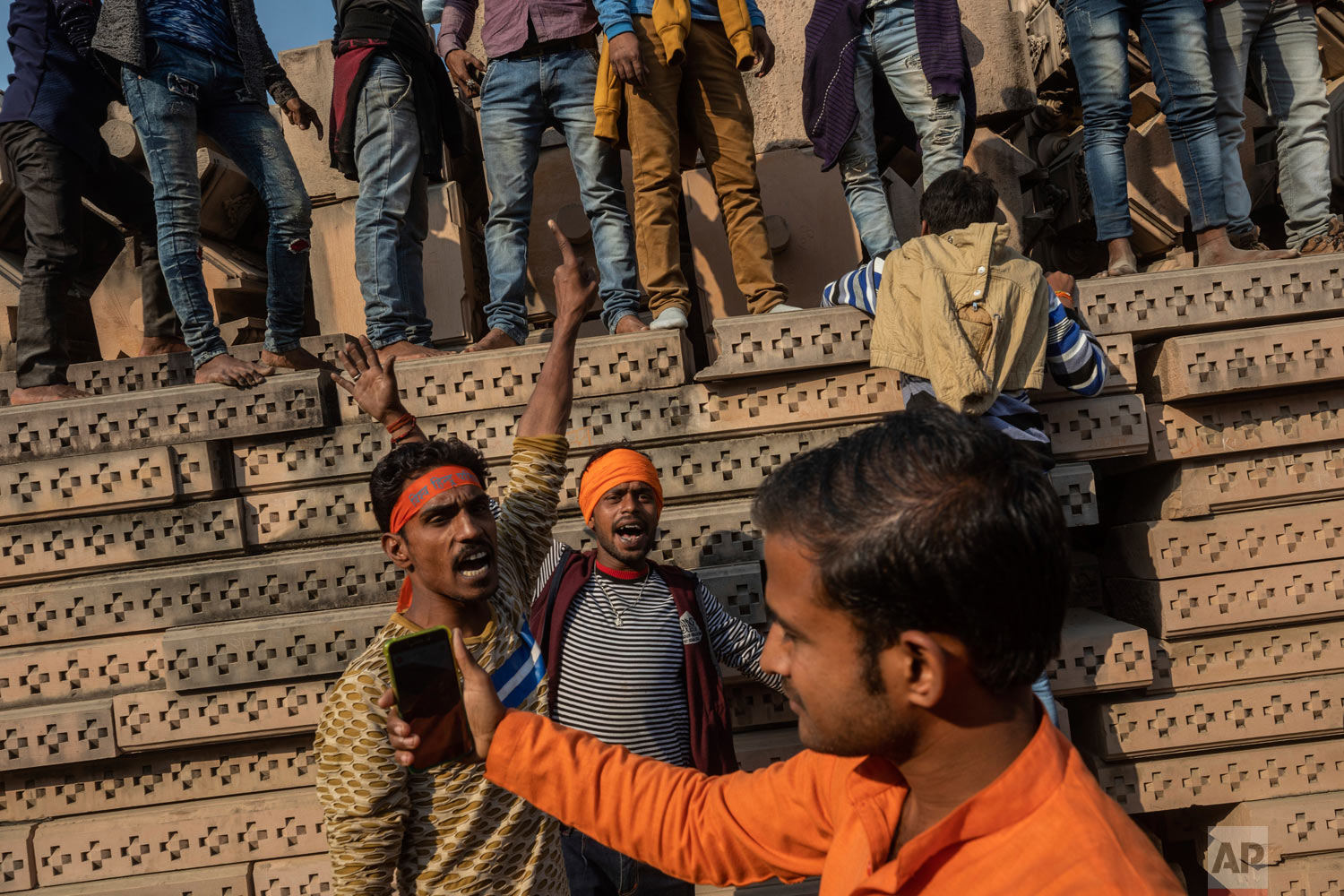 Hindu hardliners gather next to building materials to be assembled in a temple dedicated to Hindu god Ram in Ayodhya, Uttar Pradesh, India, Nov. 25, 2018. (AP Photo/Bernat Armangue)