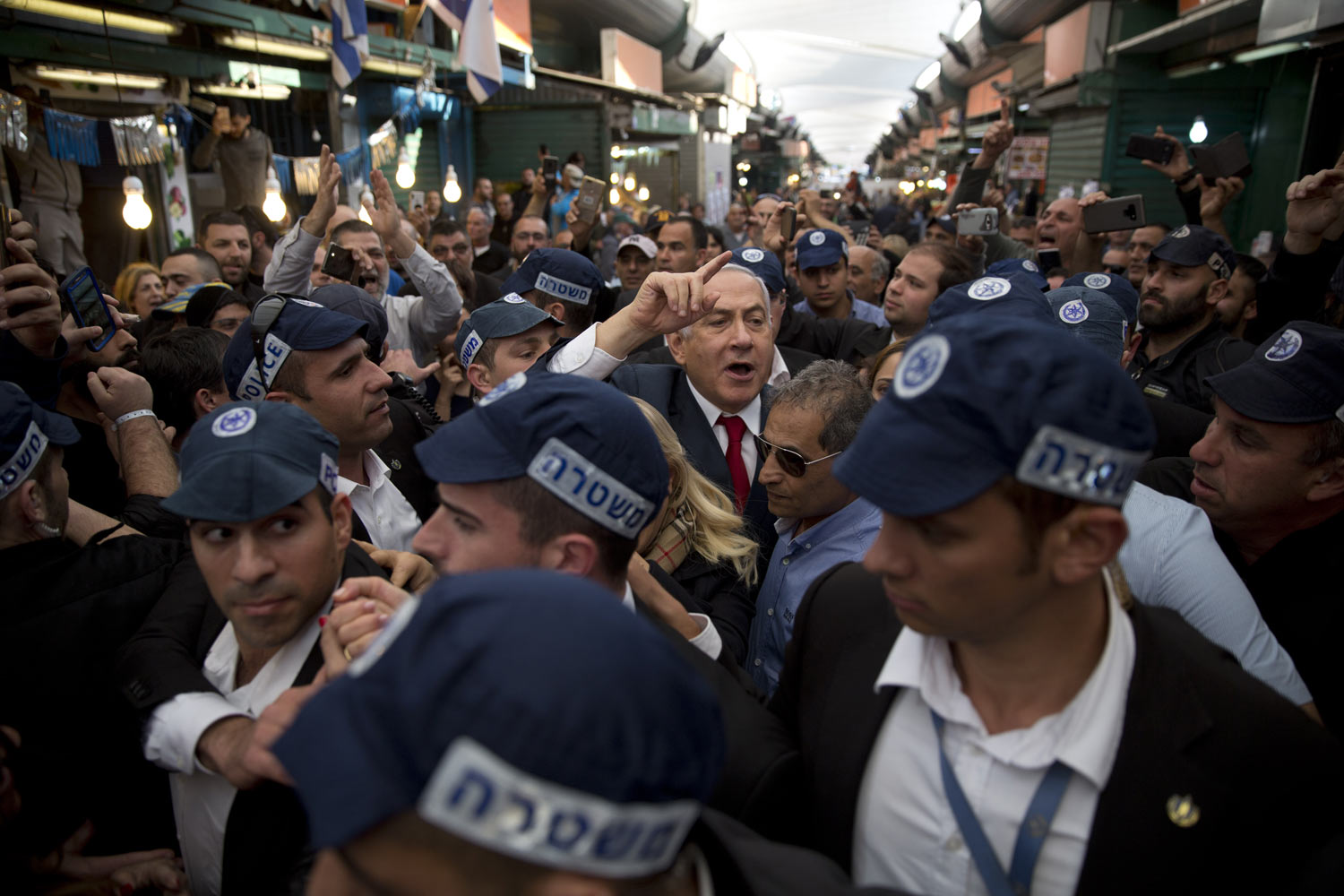 "Israeli Prime Minister Benjamin Netanyahu, head of the Likud party, center, is escorted by security guards during a visit to the Ha'tikva market in Tel Aviv, Israel, Tuesday, April 2, 2019. Twitter says it has ""taken action"" after an Israeli watchdog exposed an alleged bot network spreading propaganda in support of Prime Minister Benjamin Netanyahu and smearing his opponents. (AP Photo/Oded Balilty)"