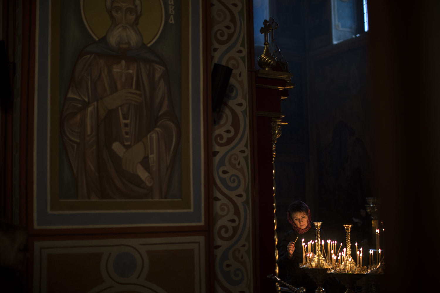 A worshiper lights candles inside Mikhailovsky cathedral in Kiev, Ukraine, on Saturday, March 30, 2019, a day before the first round of presidential elections. (AP Photo/Emilio Morenatti)
