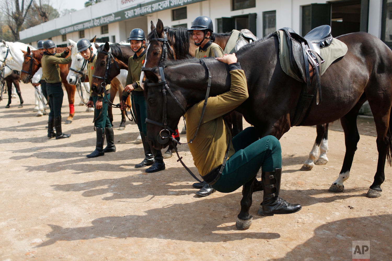 A Nepalese army soldier plays with his horse as others watch before leaving for rehearsals for Ghode Jatra festival on March 19, 2019, in Kathmandu, Nepal. (AP Photo/Niranjan Shrestha)