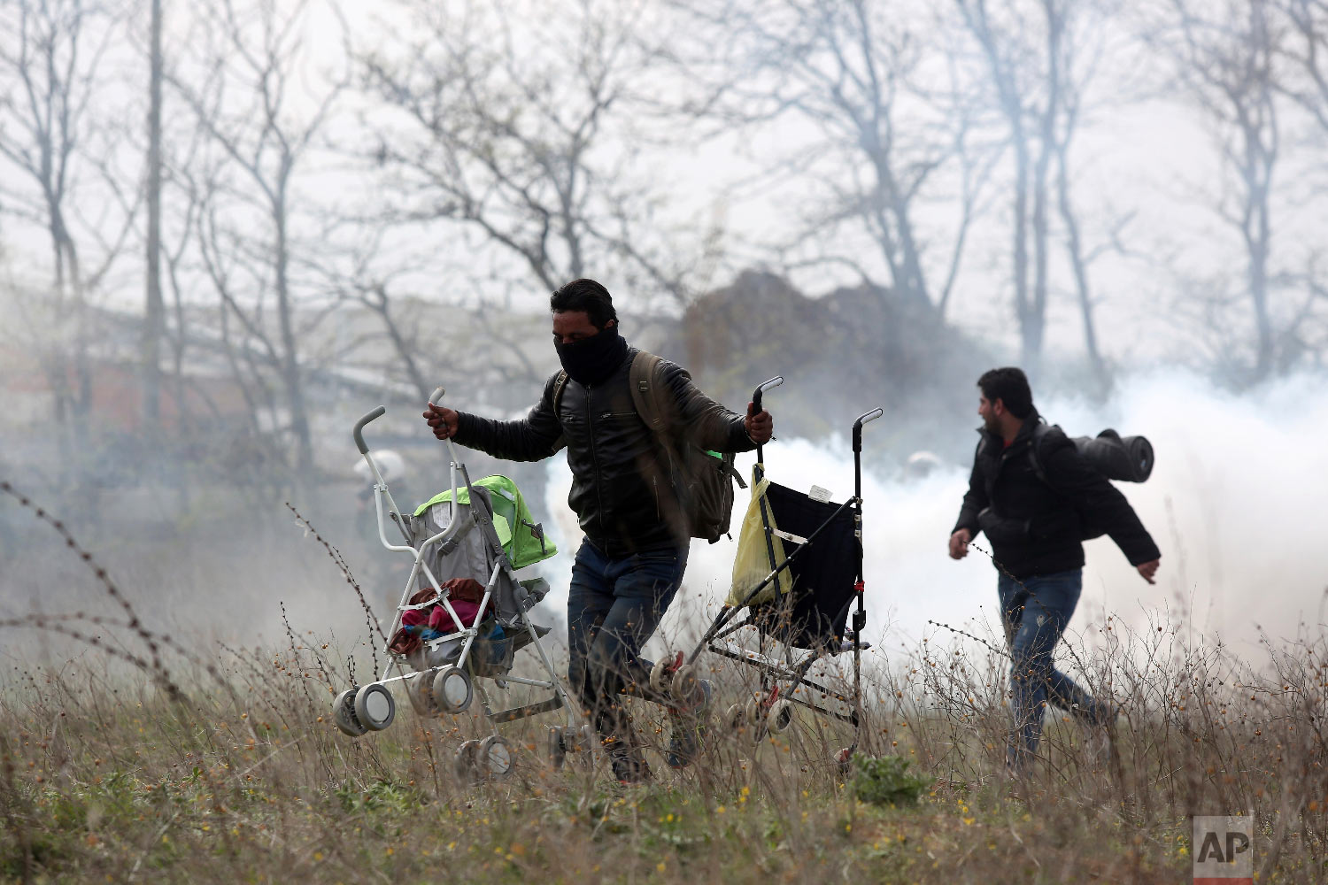A man holding two baby strollers runs to avoid tear gas thrown by riot police during clashes outside a refugee camp in the village of Diavata, west of Thessaloniki, northern Greece, Friday, April 5, 2019. (AP Photo/Giannis Papanikos)