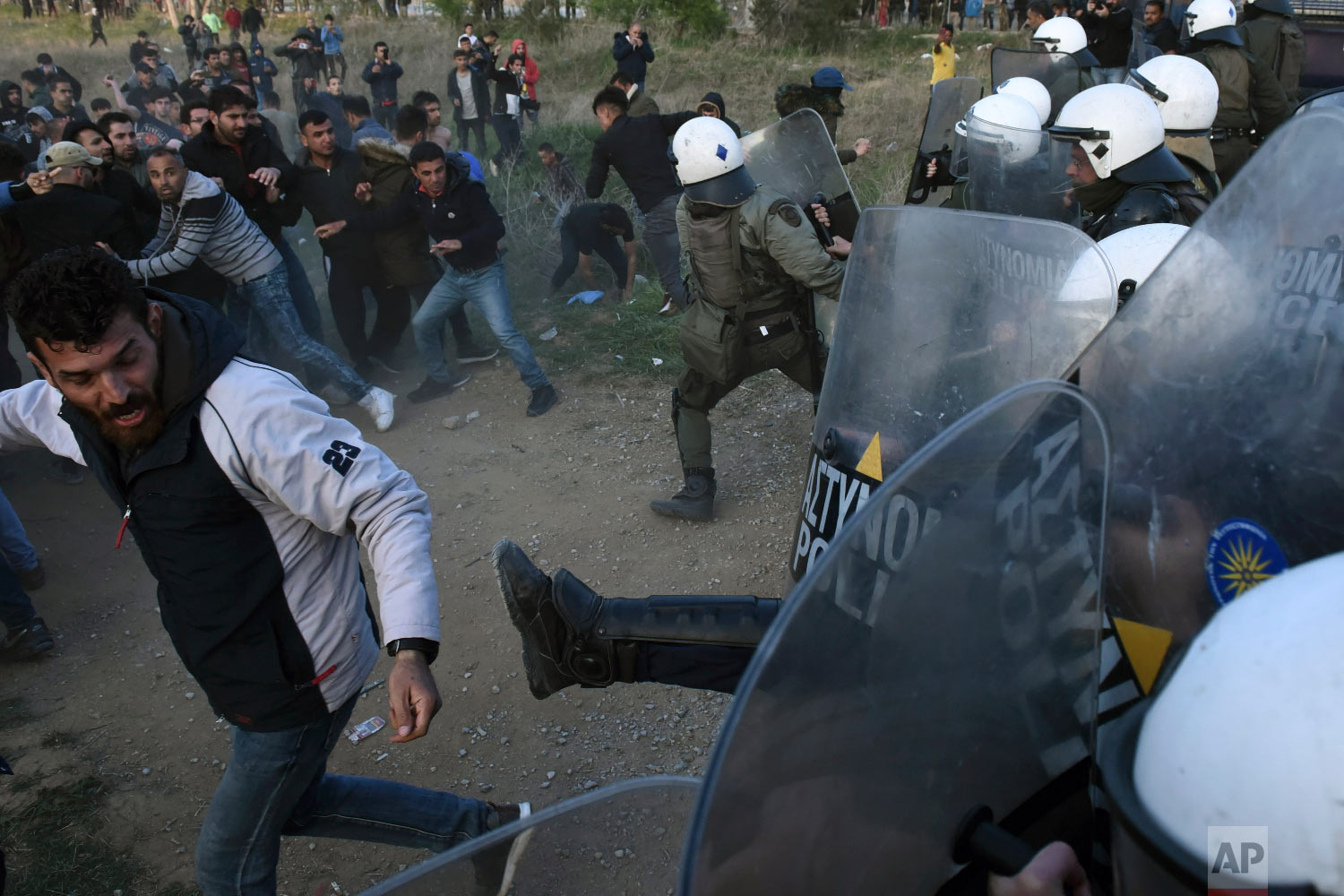 Migrants clash with riot police during a rally outside a refugee camp in the village of Diavata, west of Thessaloniki, northern Greece, Thursday, April 4, 2019. (AP Photo/Giannis Papanikos)