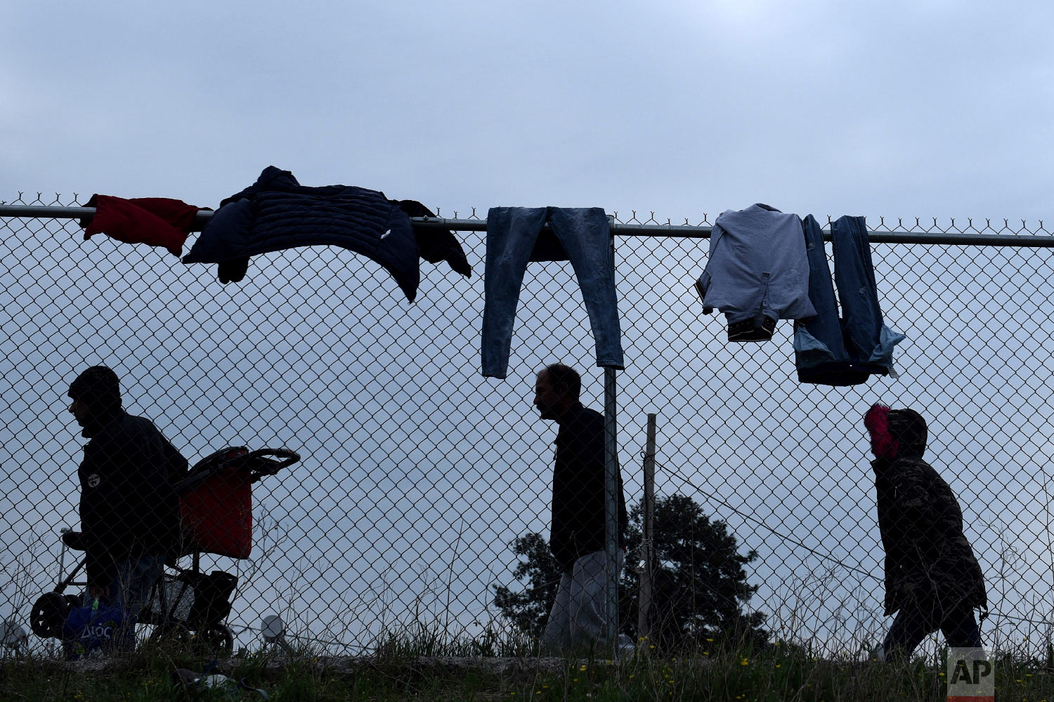 Migrants walk by a refugee camp in the village of Diavata, west of Thessaloniki, northern Greece, Friday, April 5, 2019. (AP Photo/Giannis Papanikos)