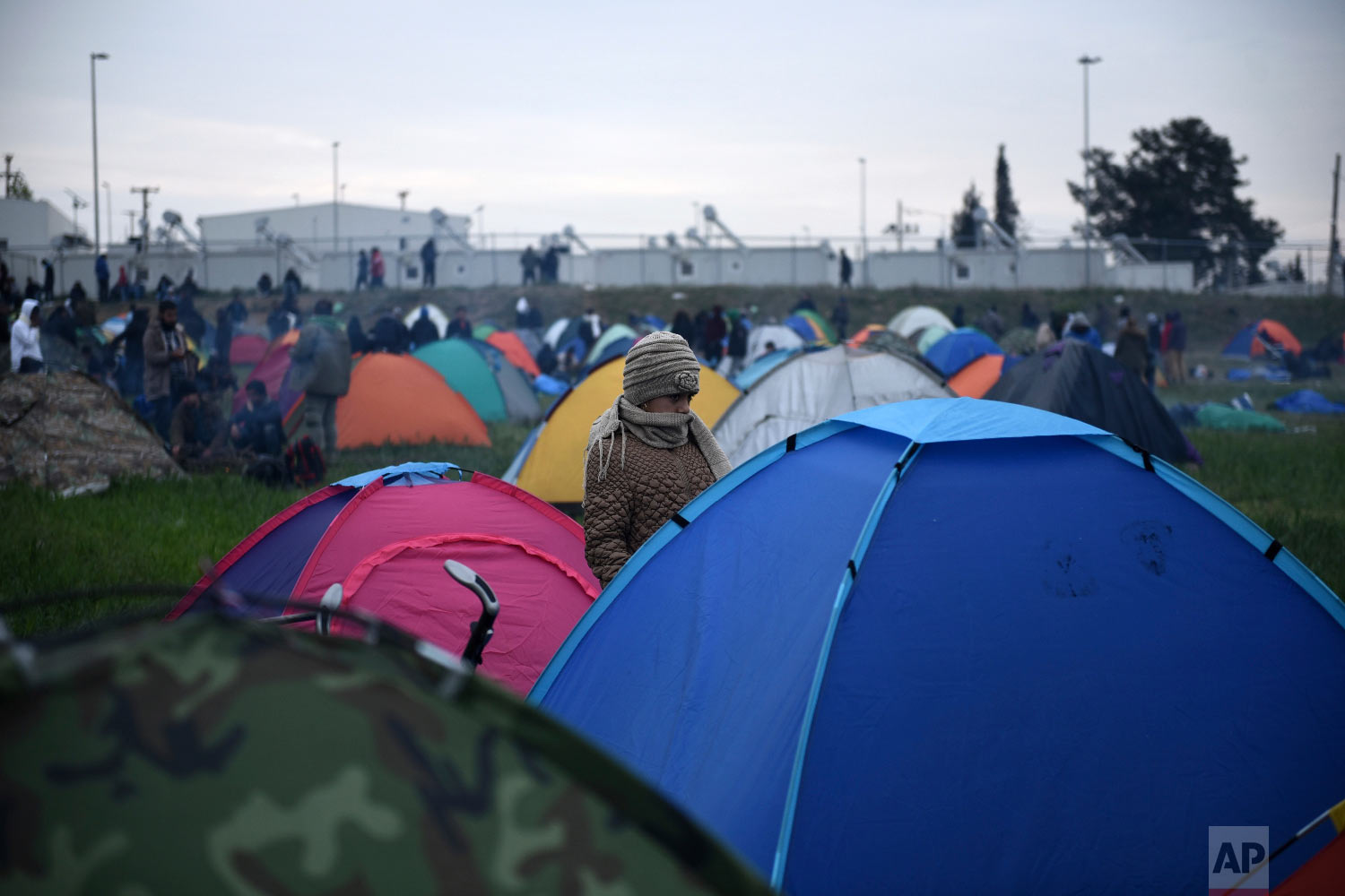 A girl stands next to a tent outside a refugee camp in the village of Diavata, west of Thessaloniki, northern Greece, Friday, April 5, 2019. (AP Photo/Giannis Papanikos)