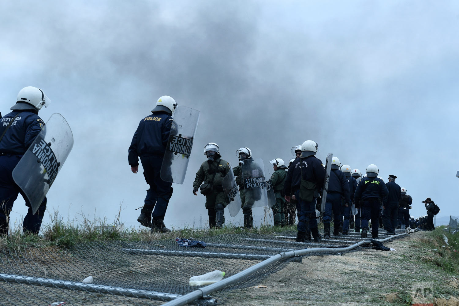 Riot police stand on a fallen fence of a refugee camp in the village of Diavata, west of Thessaloniki, northern Greece, Saturday, April 6, 2019. (AP Photo/Giannis Papanikos)