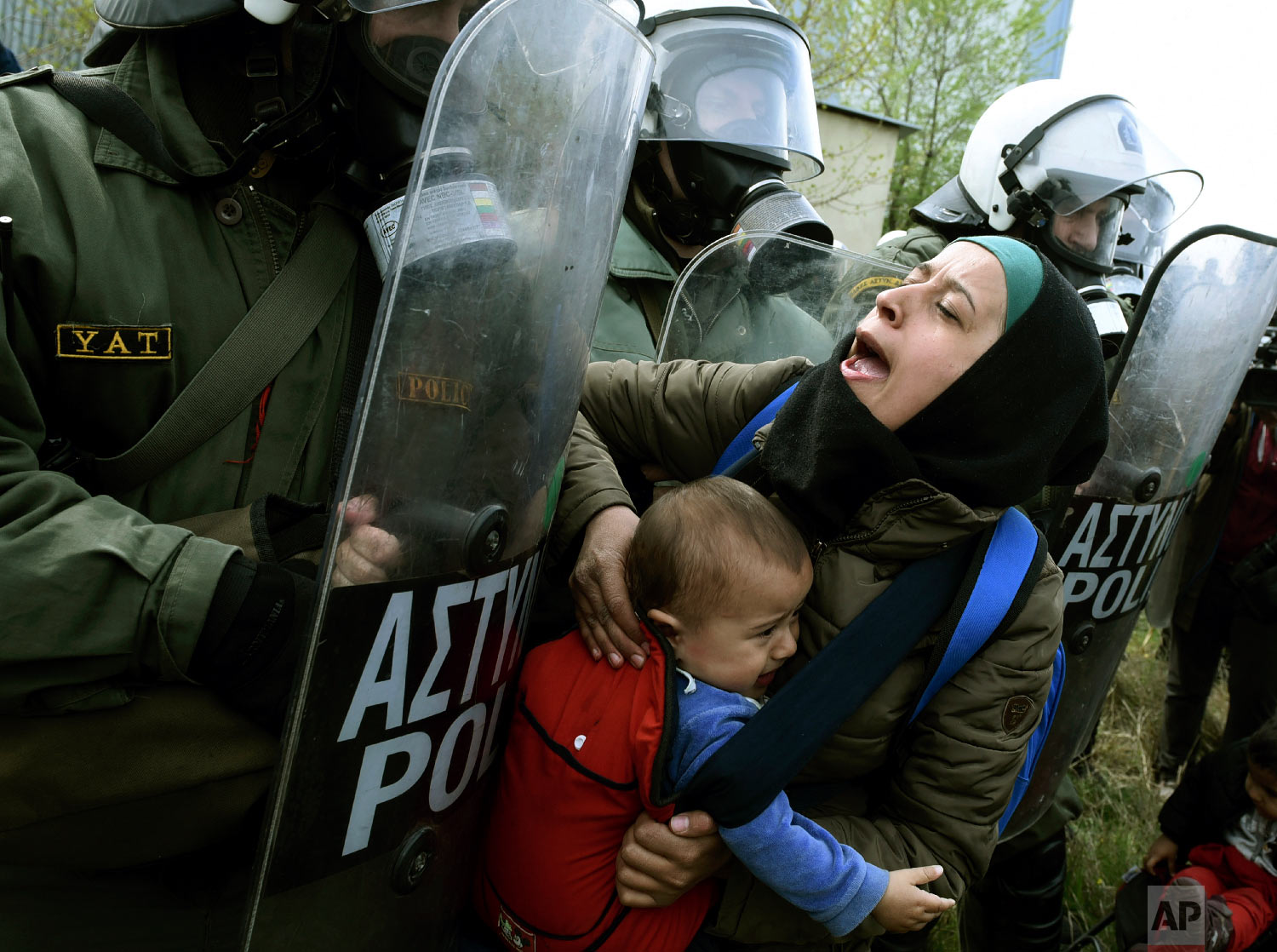 A migrant woman with a child pushing with riot police outside a refugee camp in the village of Diavata, west of Thessaloniki, northern Greece, Friday, April 5, 2019. (AP Photo/Giannis Papanikos)