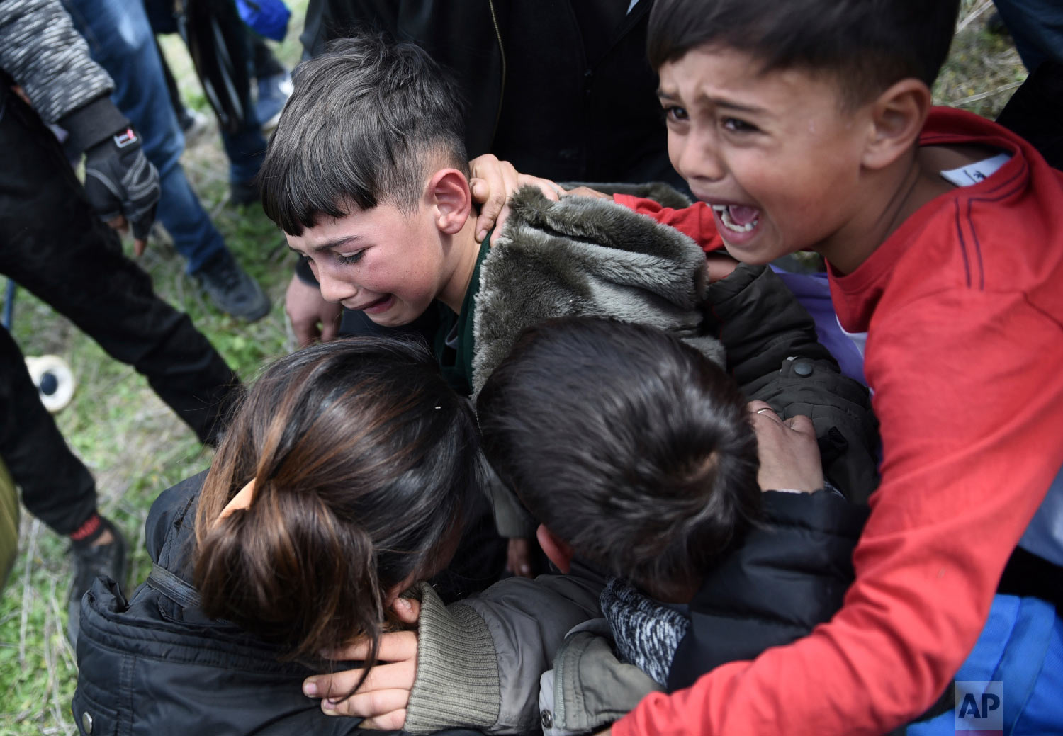 Children cry after police used tear gas during clashes outside a refugee camp in the village of Diavata, west of Thessaloniki, northern Greece, Friday, April 5, 2019. (AP Photo/Giannis Papanikos)