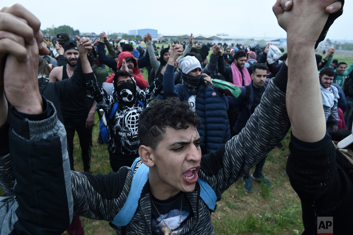 Protesting migrants shout slogans during a rally outside a refugee camp in the village of Diavata, west of Thessaloniki, northern Greece, Saturday, April 6, 2019. (AP Photo/Giannis Papanikos)