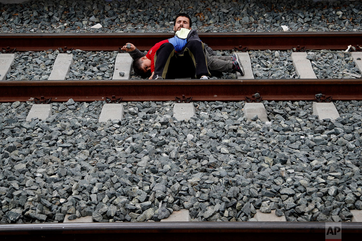 A migrant father with his child lays on the rail tracks at Larissis main rail station in Athens, Friday, April 5, 2019. (AP Photo/Thanassis Stavrakis)