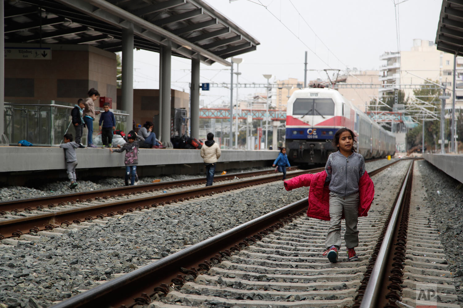 A migrant boy walks at the rail wall that blocked from migrants at the Larissis rail way central station in Athens, Friday, April 5, 2019. (AP Photo/Thanassis Stavrakis)