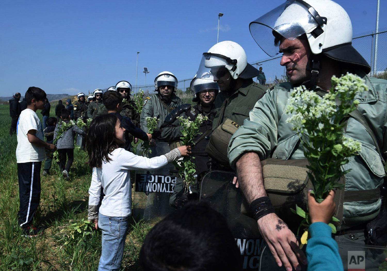 Children of migrants offer flowers to riot police during a rally outside a refugee camp in the village of Diavata, west of Thessaloniki, northern Greece, Thursday, April 4, 2019. (AP Photo/Giannis Papanikos)