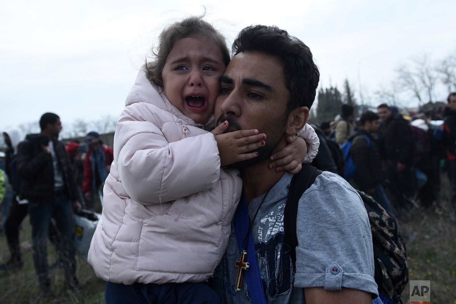 A man holds a crying girl as riot police use tear gas during clashes outside a refugee camp in the village of Diavata, west of Thessaloniki, northern Greece, Friday, April 5, 2019. (AP Photo/Giannis Papanikos)