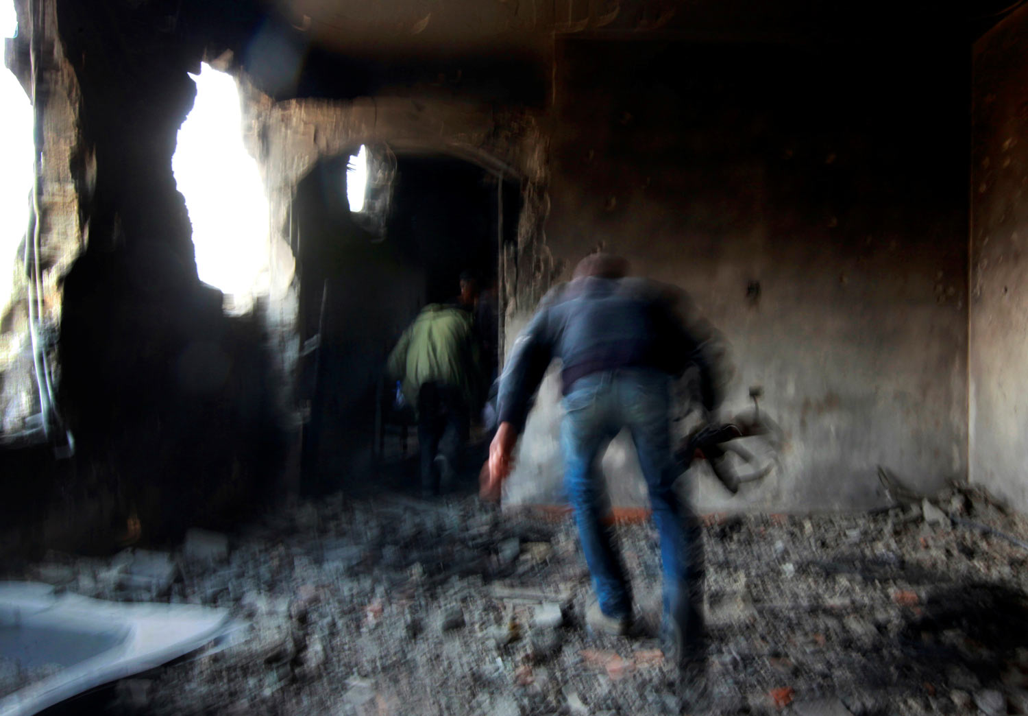 Rebel fighters run for cover inside a building on the frontline in Tripoli street in central Misrata, April 21, 2011. Tripoli street is the scene of some of the heaviest fighting between rebels and Gaddafi forces. (REUTERS/Yannis Behrakis)