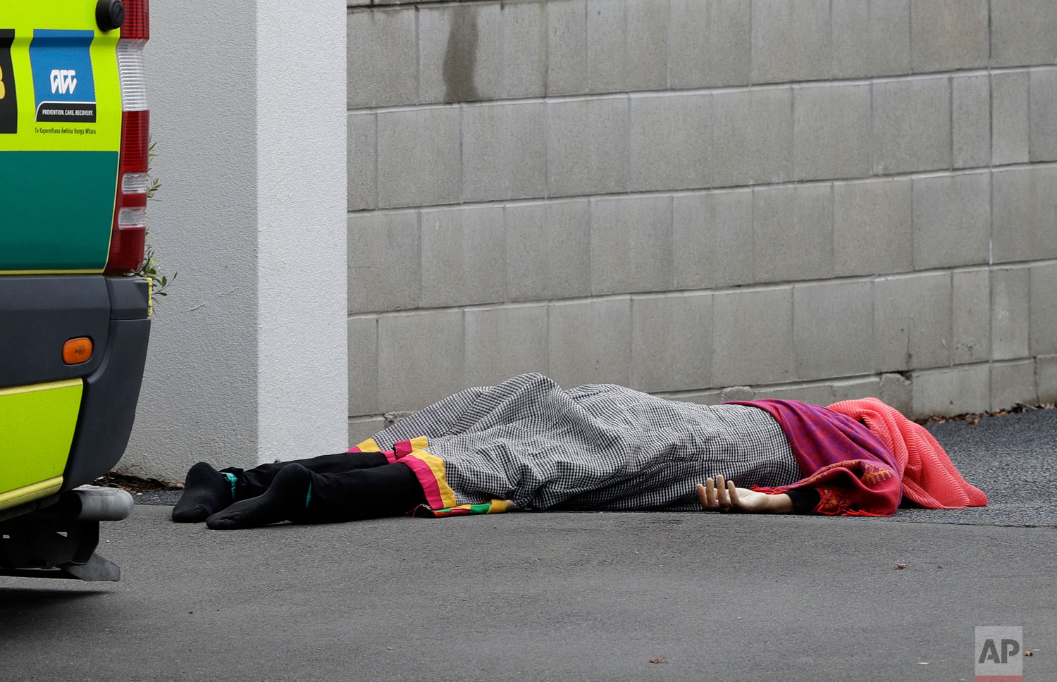 A body lies on the footpath outside a mosque in central Christchurch, New Zealand, Friday, March 15, 2019. (AP Photo/Mark Baker)