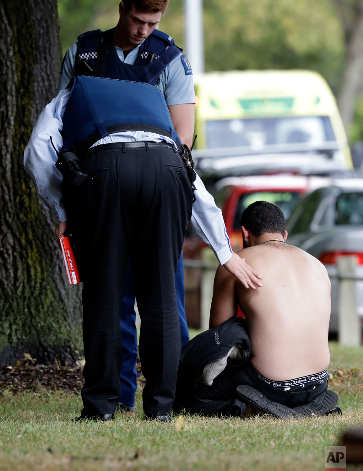 Police console a man outside a mosque in central Christchurch, New Zealand, Friday, March 15, 2019. (AP Photo/Mark Baker)