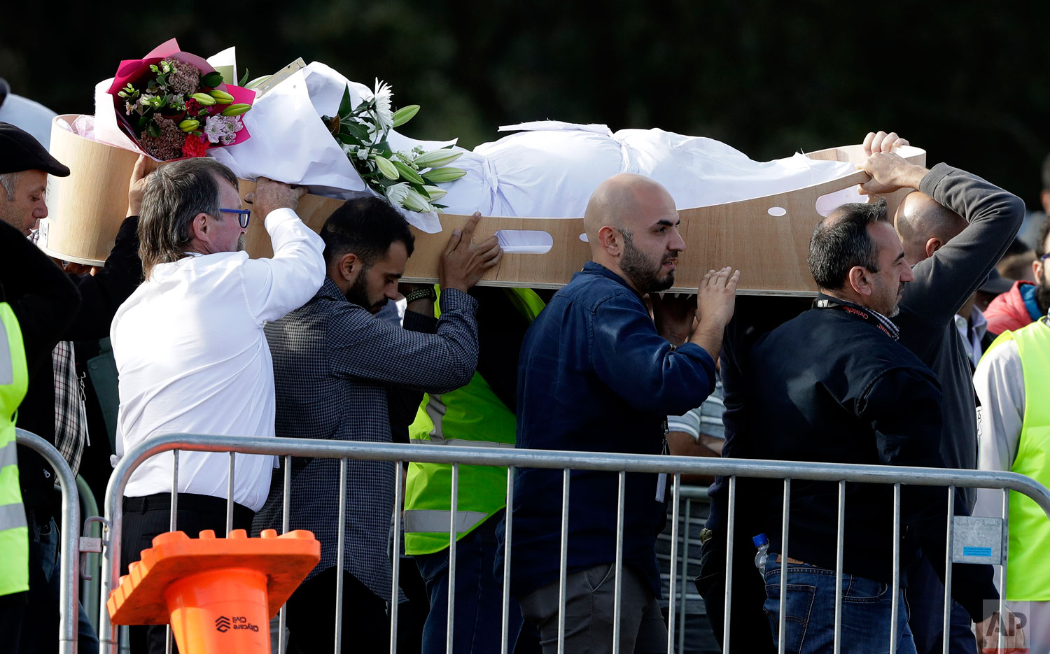 Mourners carry a body at Memorial Park Cemetery in Christchurch, New Zealand, Friday, March 22, 2019. Funerals continued following the March 15 mosque attacks where 50 worshippers were killed by a white supremacist.  (AP Photo/Mark Baker)