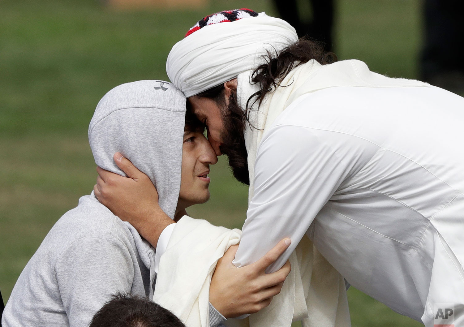 Zaid Mustafa, son and brother of victims from last week's mosque shootings is welcomed to Friday prayers at Hagley Park in Christchurch, New Zealand, Friday, March 22, 2019. Thousands of people gathered in a Christchurch city park near the Al Noor mosque where a gunman killed some of the 50 worshippers in a white supremacist attack on two mosques.  (AP Photo/Mark Baker)