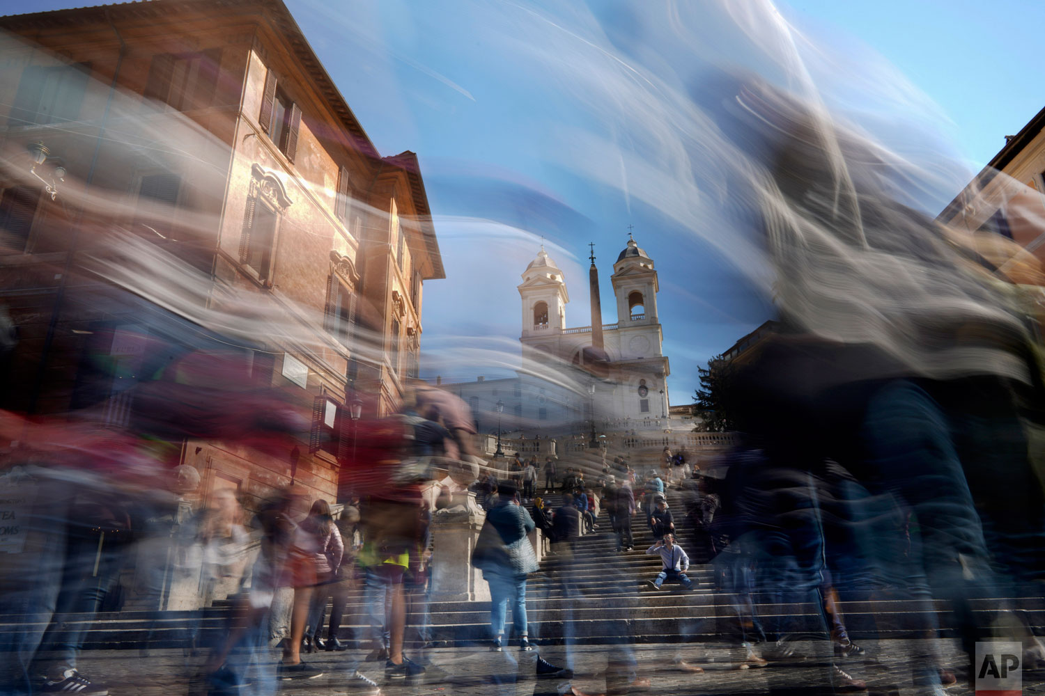 In this photo made with a long exposure, people walk by the Spanish Steps in Rome, Monday, March 25, 2019. (AP Photo/Andrew Medichini)