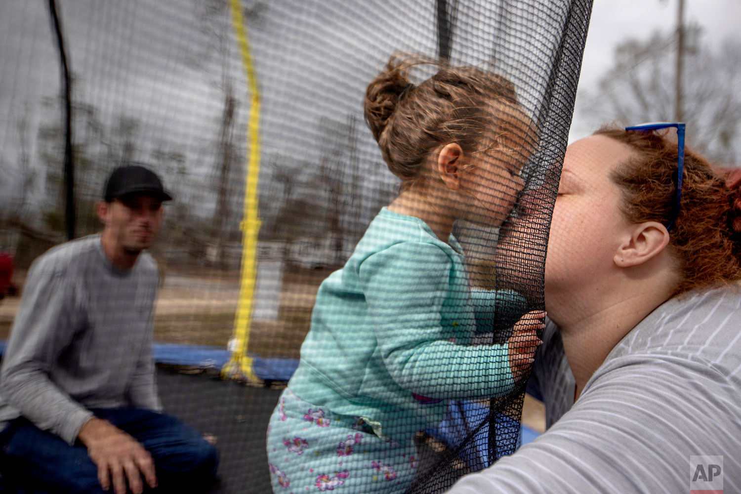 Mystie Gregory, right, kisses her twenty-month-old daughter Neala as her fiancé Gary LaPlant looks on while playing on a trampoline in the backyard where several local residents are living in tents after becoming homeless from Hurricane Michael in Youngstown, Fla, Wednesday, Jan. 23, 2019. Gregory said they left their apartment for several days to take a break from living without electricity. When they got back, she says, it had been rented to another family. (AP Photo/David Goldman)