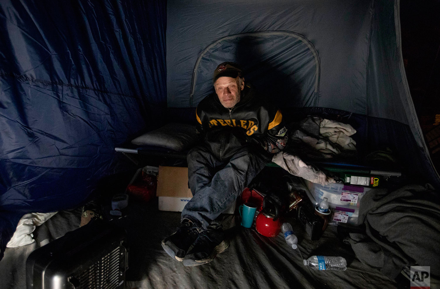 James Huebner sits in his tent in the backyard of a home where he's living with his son and brother after becoming homeless from Hurricane Michael in Youngstown, Fla, Wednesday, Jan. 23, 2019. Huebner has never been homeless before and says they can't find any affordable available housing in the area where they need to remain because of his brother's job at a nearby Walmart store. (AP Photo/David Goldman)