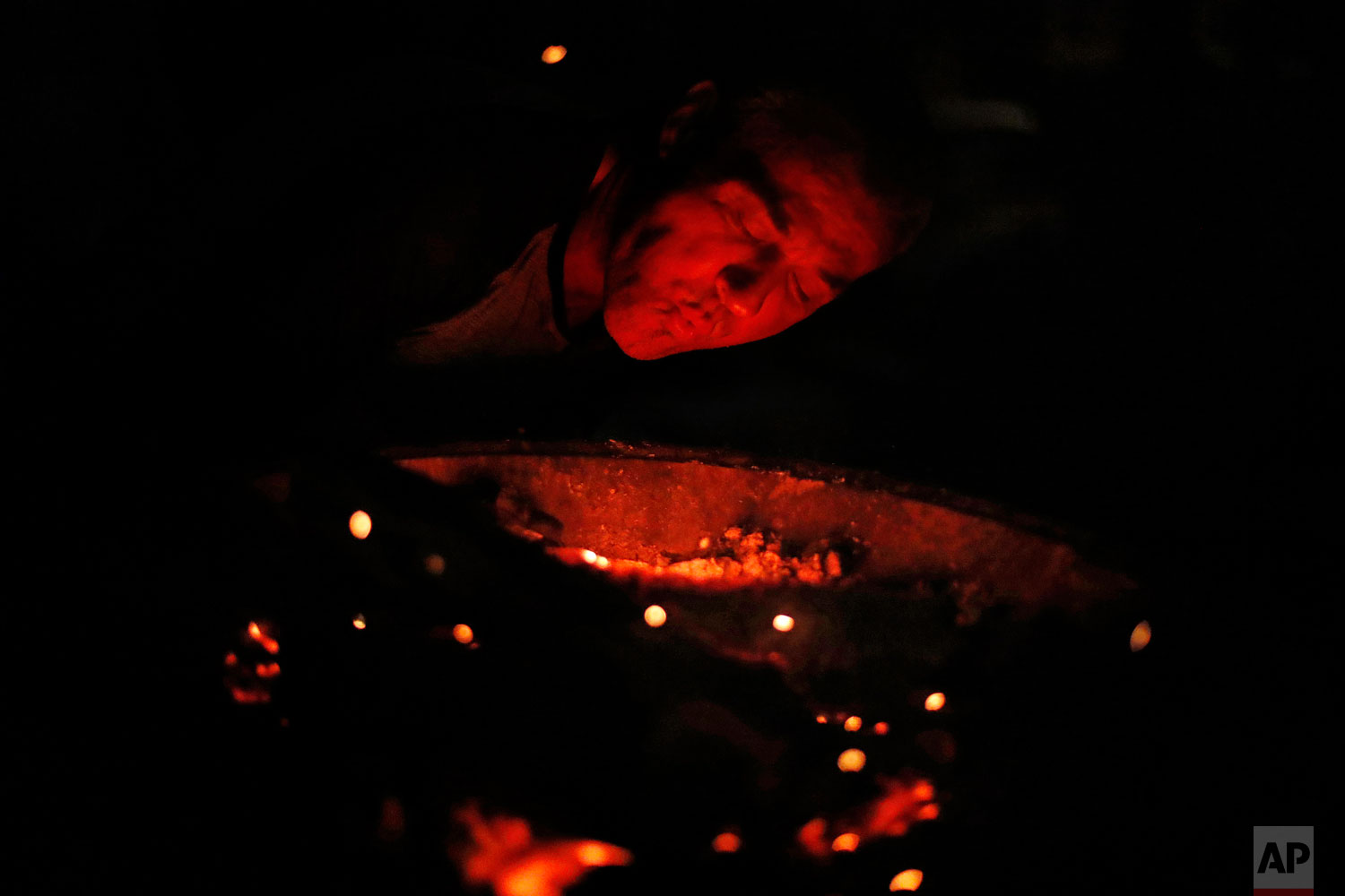 Gene Hogan blows on a campfire outside the tent he's living in since becoming homeless from Hurricane Michael in Youngstown, Fla, Wednesday, Jan. 23, 2019. Hotel vouchers and trailers provided by the Federal Emergency Management Agency are helping ease the pain, but for many residents living in tents is their only option. (AP Photo/David Goldman)