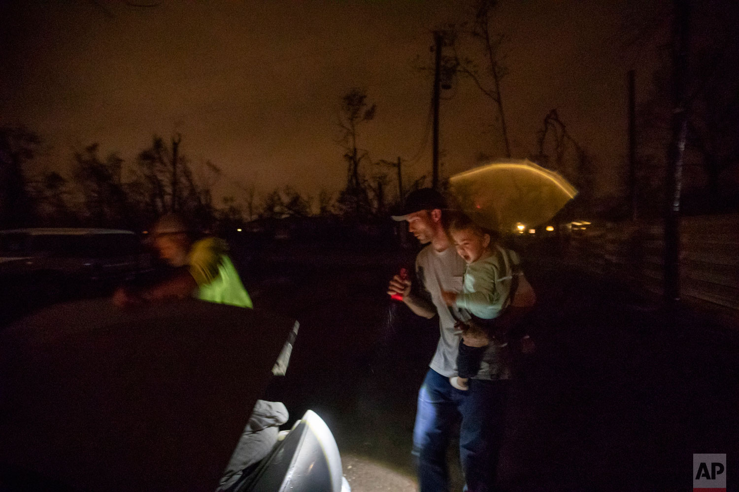 "Twenty-month-old Neala Clark cries as her mother's fiancé, Gary LaPlant, loads their personal belongings from the tent they're living in into a car taking them to a halfway home LaPlant found for them in the middle of a rain storm in Youngstown, Fla, Wednesday, Jan. 23, 2019. After the family spent the night at the halfway home, they planned to return the next day to live in their tent in the Summer's backyard where they feel more comfortable. ""It's such a positive environment out there despite the mess everyone had gone through,"" said LaPlant's fiancee, Mystie Gregory. (AP Photo/David Goldman)"