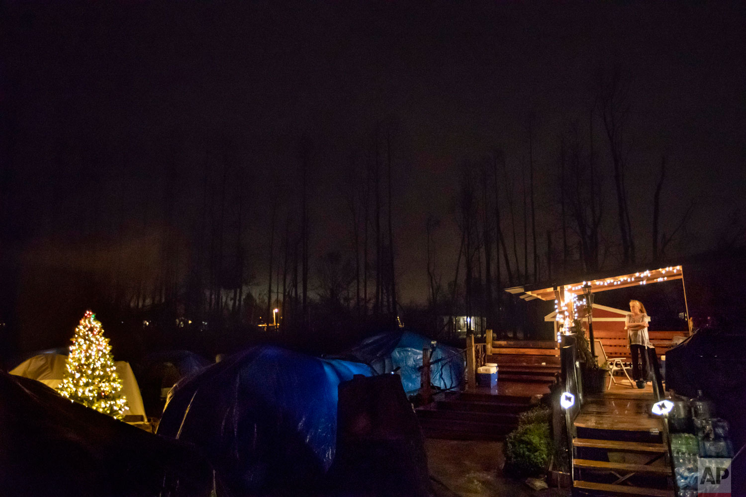"Diahnn ""Shelly"" Summers, right, looks out over the tents she set up in her backyard for  homeless Hurricane Michael evacuees in Youngstown, Fla, Wednesday, Jan. 23, 2019. ""There is nowhere for them to go,"" Summers said. ""When you don't have a home, you have no sense of safety, no sense of belonging, no security. You don't even know where you're going to sleep without getting into trouble. It's the worst feeling."" (AP Photo/David Goldman)"