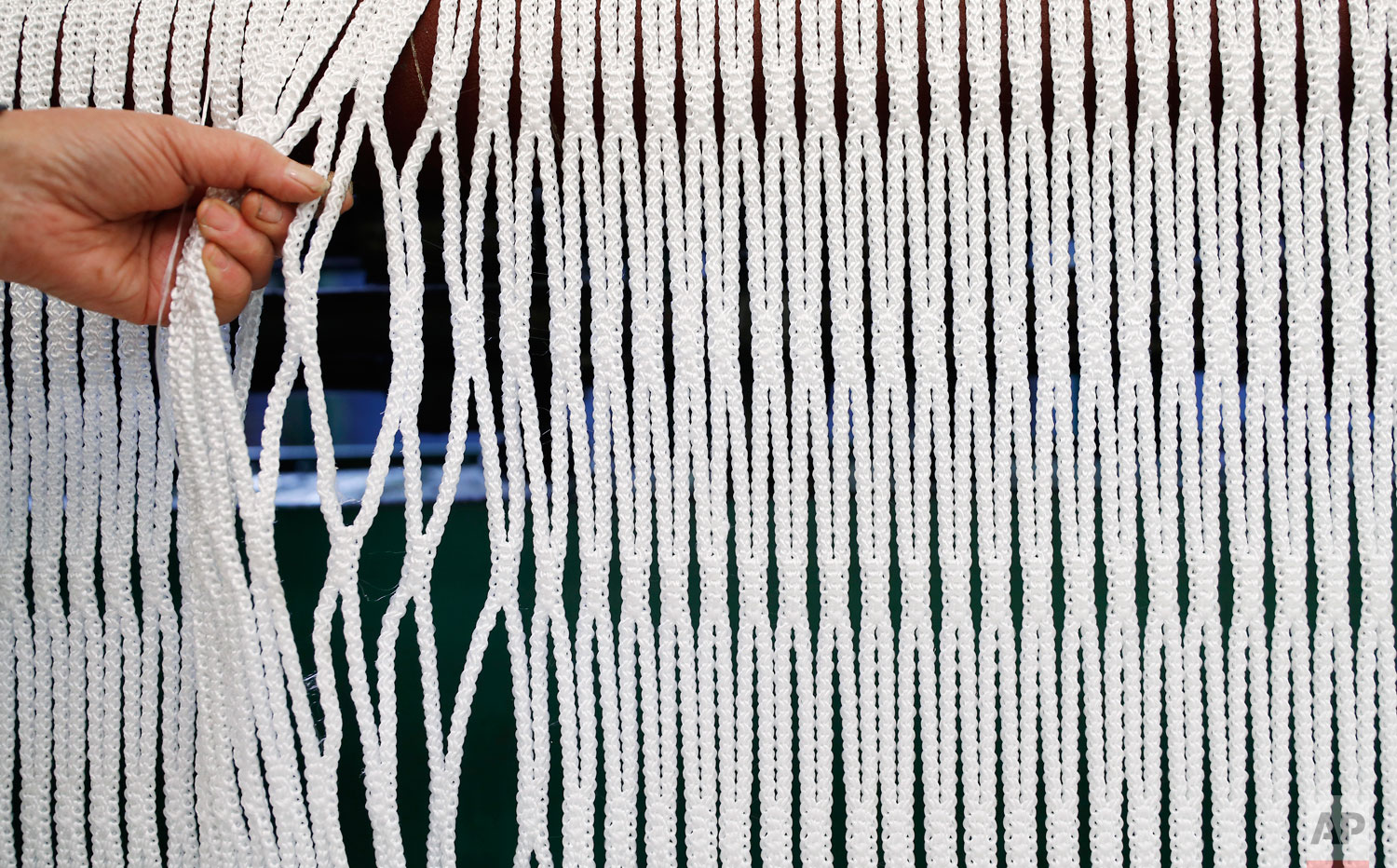 "In this photo taken on Thursday, Feb. 7, 2019, a woman works at ""La Rete"" (The Net) factory in Monte Isola, Lake Iseo, northern Italy. Step off the ferry onto Monte Isola and it feels like going back in time.  (AP Photo/Antonio Calanni)"