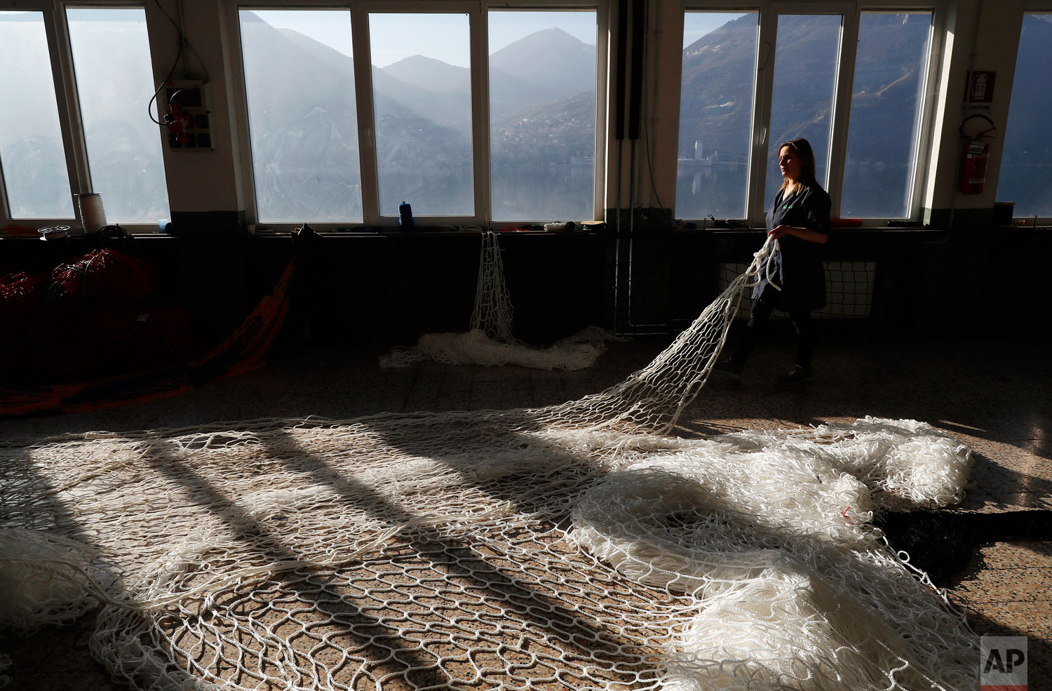 "In this photo taken on Wednesday, Feb. 6, 2019, a woman works at ""La Rete"" (The Net) factory in Monte Isola, Lake Iseo, northern Italy.  (AP Photo/Antonio Calanni)"