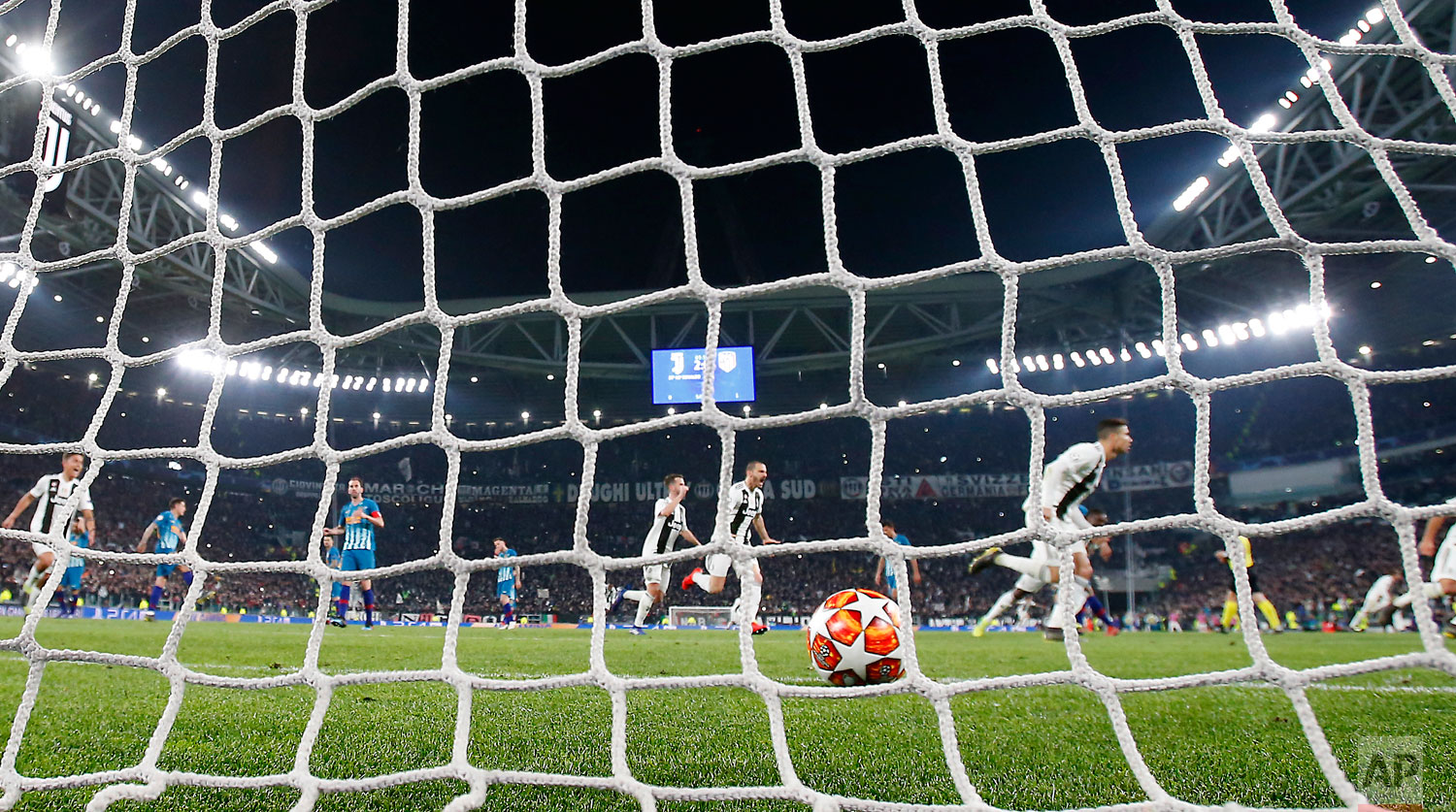 "In this photo taken on Tuesday, March 12, 2019 through a net made by ""La Rete"" factory,  Juventus' Cristiano Ronaldo celebrates after scoring his side's third goal during the Champions League round of 16, 2nd leg, soccer match between Juventus and Atletico Madrid at the Allianz stadium in Turin, Italy. Step off the ferry onto Monte Isola and it feels like going back in time. The factory of La Rete S.r.l. _ an old-fashioned producer of nets for soccer goals _ is indeed a throwback. Workers still use their hands to weave the nets that have been used at World Cups stretching back to the 1990 tournament in Italy, throughout Serie A and in recent Champions League finals, too. (AP Photo/Antonio Calanni)"
