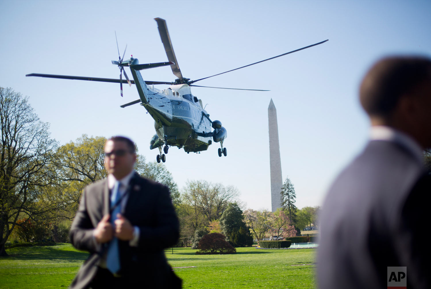 Members of the Secret Service stand on the South Lawn of the White House as Marine One helicopter, with President Donald Trump aboard, lifts off enroute to nearby Andrews Air Force Base, Md., for a trip to Texas, April 10, 2019. (AP Photo/Pablo Martinez Monsivais)