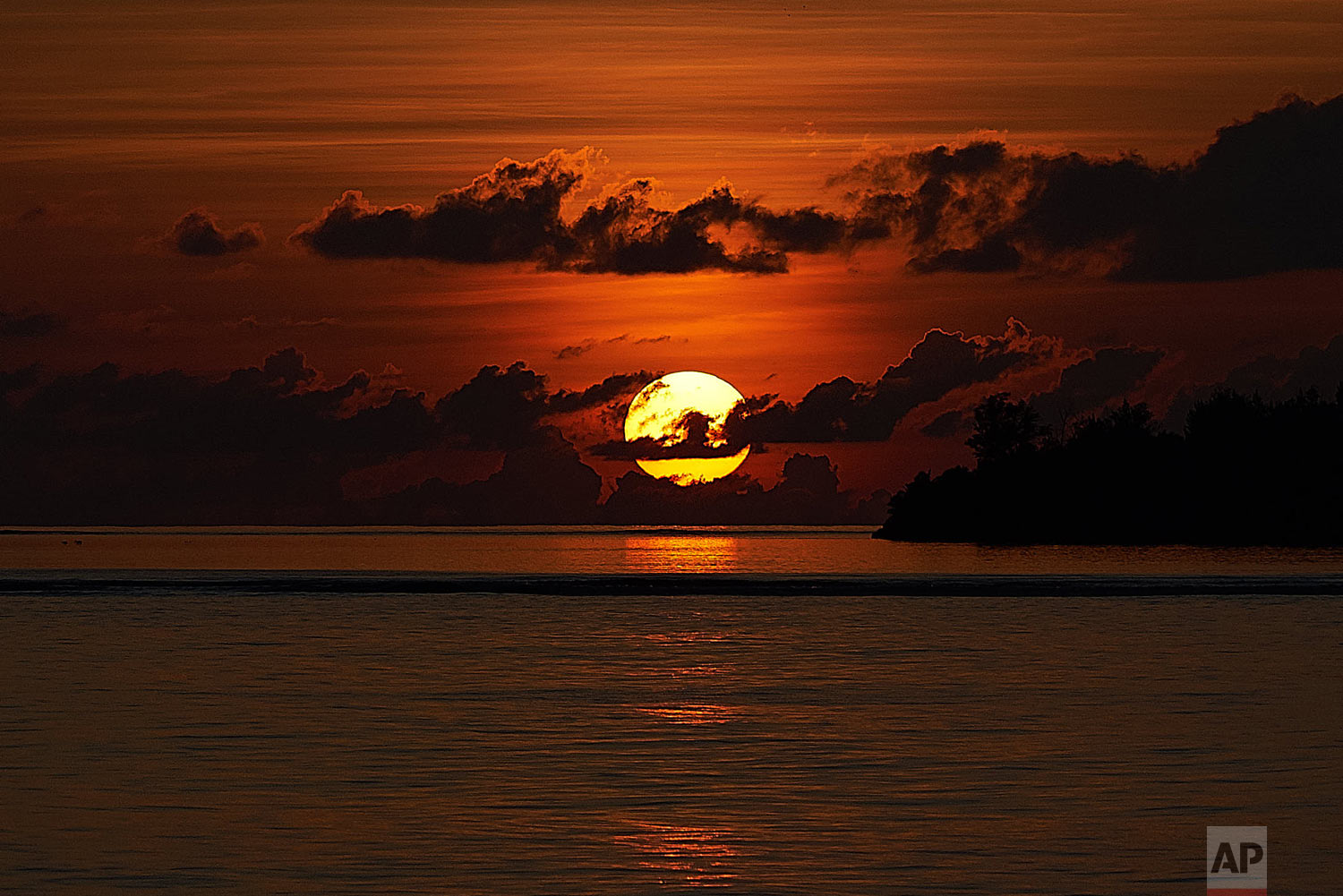 The sun sets over the island of Poivre in the Seychelles, April 5, 2019. (AP Photo/David Keyton)