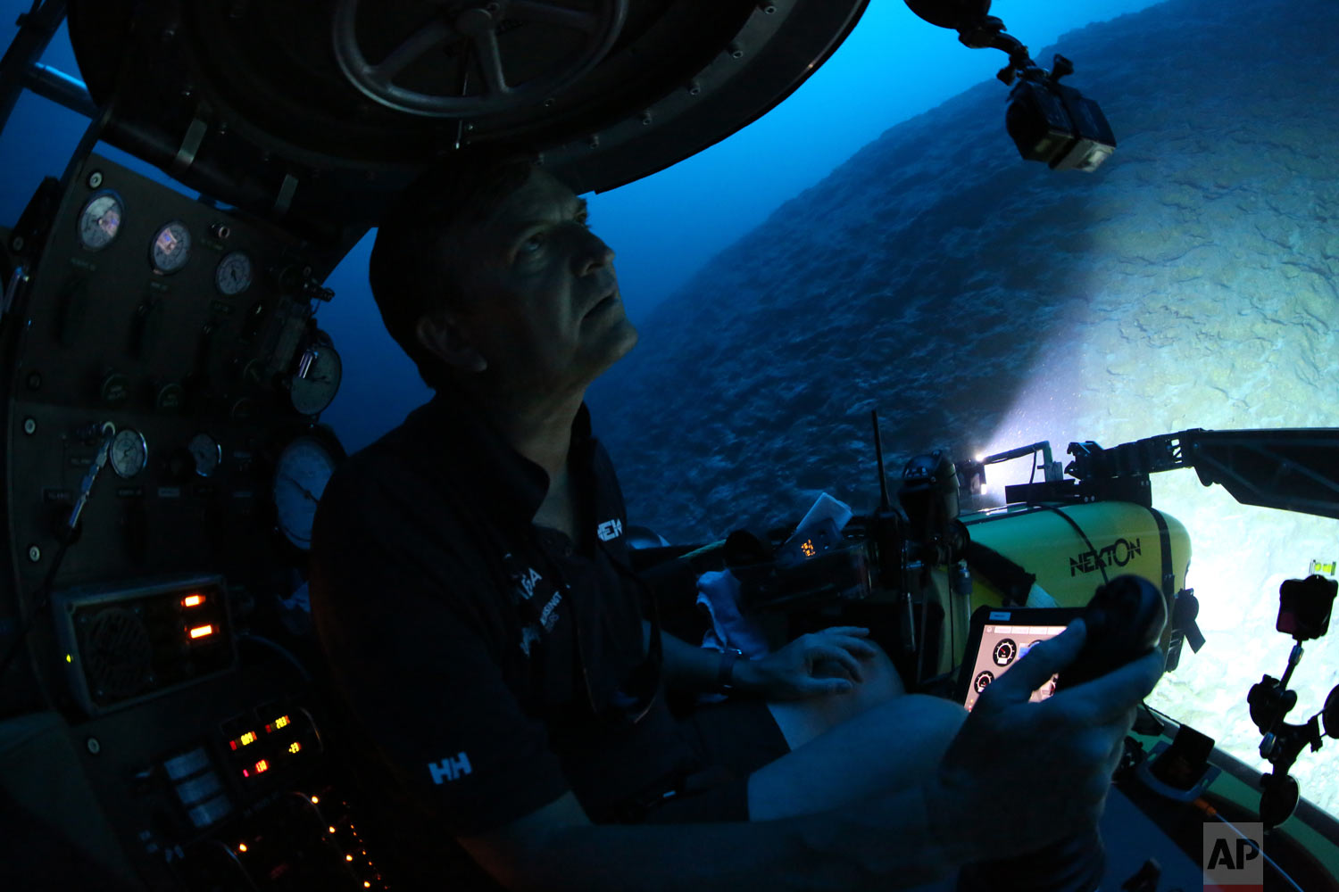 Aquanaut Robert Carmichael looks out of the submersible as he navigates strong currents during a dive to 400 feet below the surface on April 8, 2019. (AP Photo/David Keyton)
