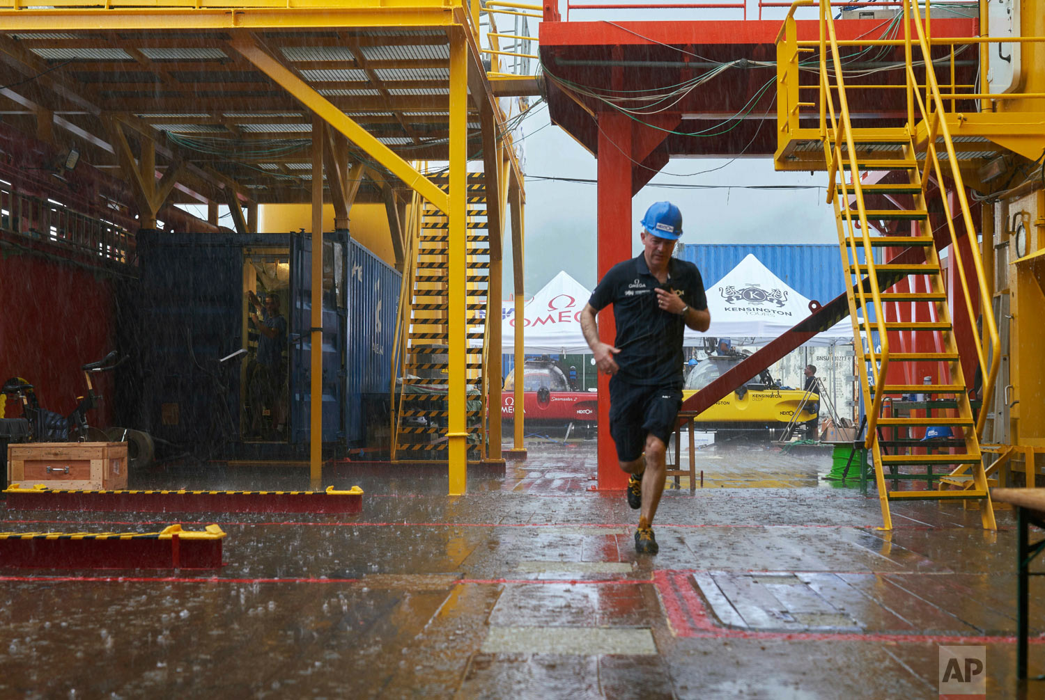 Nekton Mission Director, Oliver Steeds, runs across the deck of the Ocean Zephyr, March 4, 2019, during a rainstorm that momentarily paused preparations for the 7-week long expedition. (AP Photo/David Keyton)