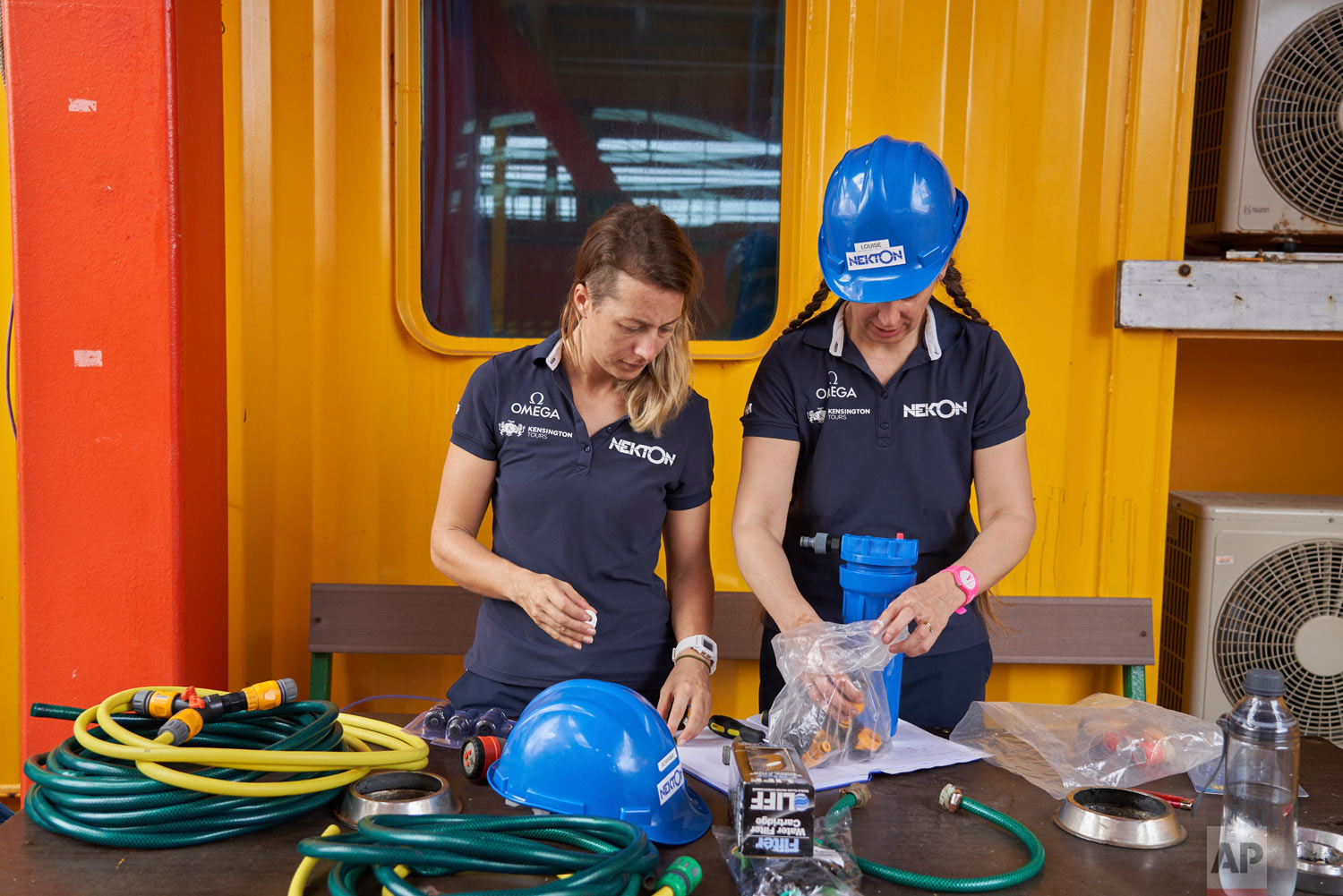 Researchers Roxana Walton, left, and Louise Allcock prepare equipment ahead the first science tasks of the British-led Nekton Mission in the tiny atoll of Alphonse in Seychelles waters, March 7, 2019. (AP Photo/David Keyton)