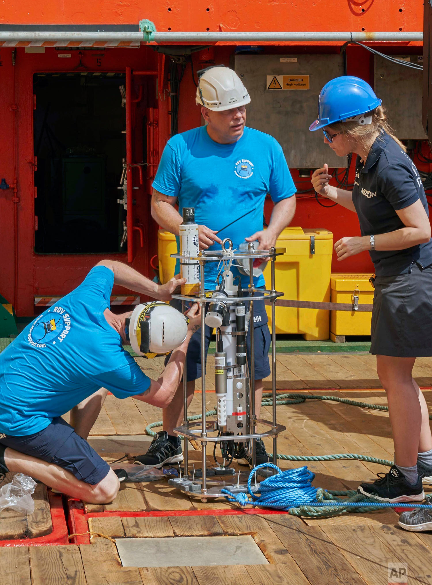 Researchers prepare a water measurement device, called CTD, as the British-led Nekton Mission begins preparations in the Indian Ocean, March 7, 2019. (AP Photo/David Keyton)