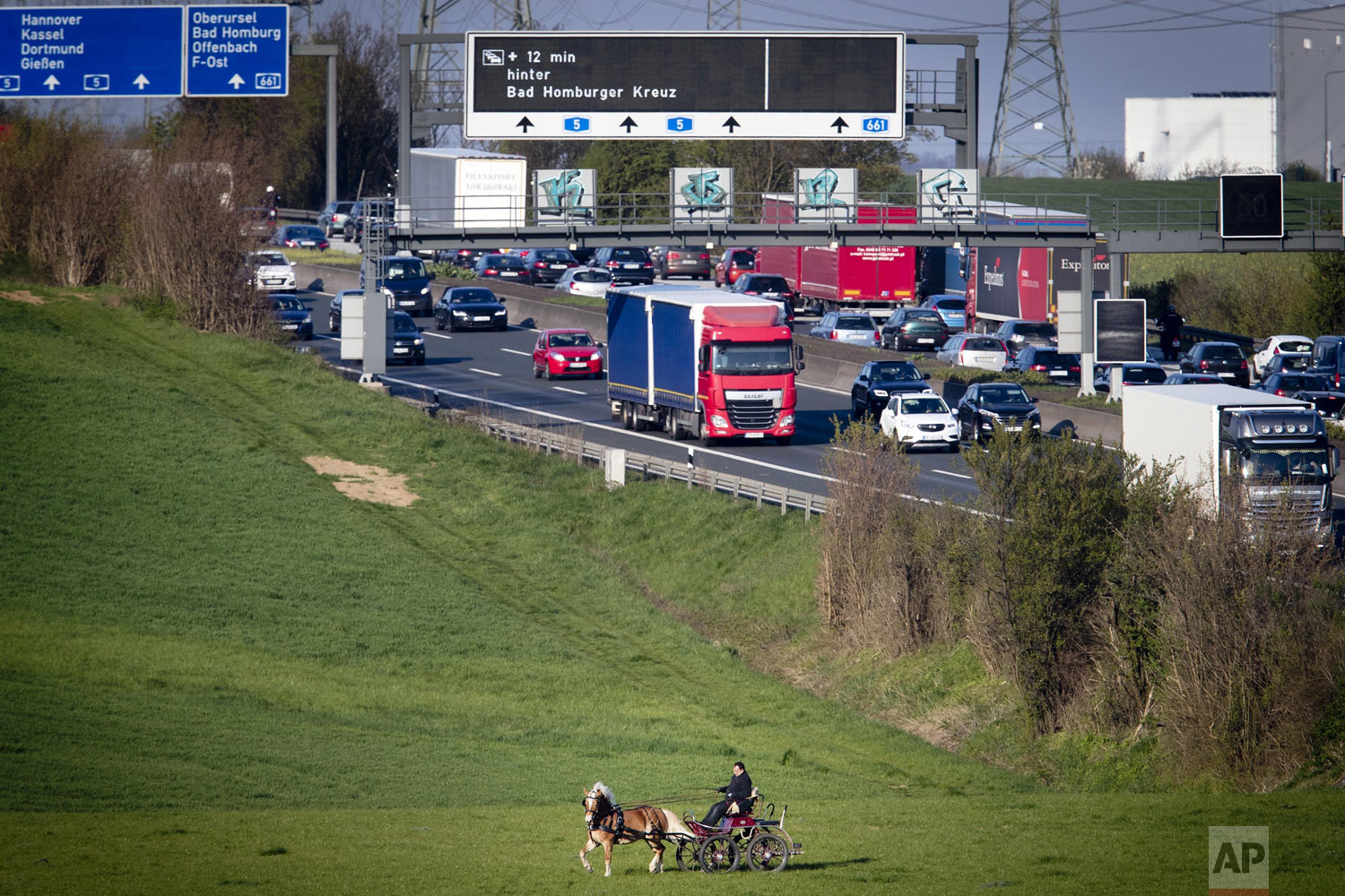A man rides his horse and carriage over a meadow near a highway in Frankfurt, Germany, on Thursday, April 11, 2019. (AP Photo/Michael Probst)