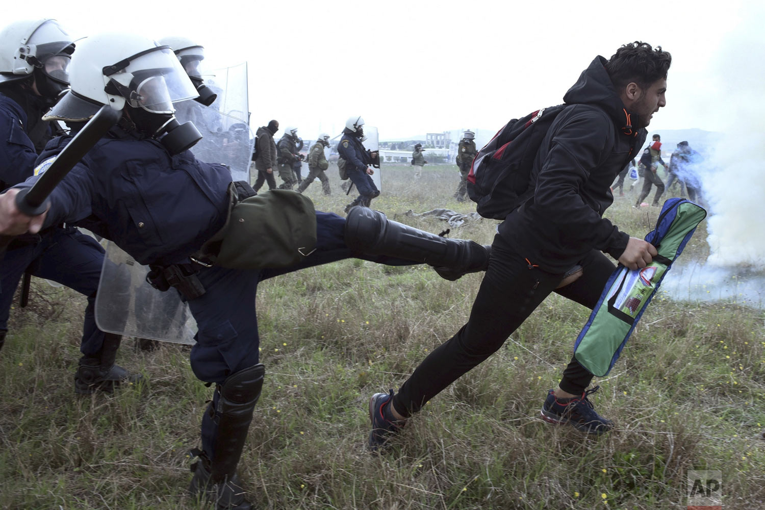 A police officer kicks a protesting migrant during clashes outside a refugee camp in the village of Diavata, west of Thessaloniki, northern Greece, Saturday, April 6, 2019. Clashes between hundreds of protesting migrants and police continued for a third day outside the overcrowded camp, with migrants throwing rocks at police and the police responding with tear gas and stun grenades. (AP Photo/Giannis Papanikos)