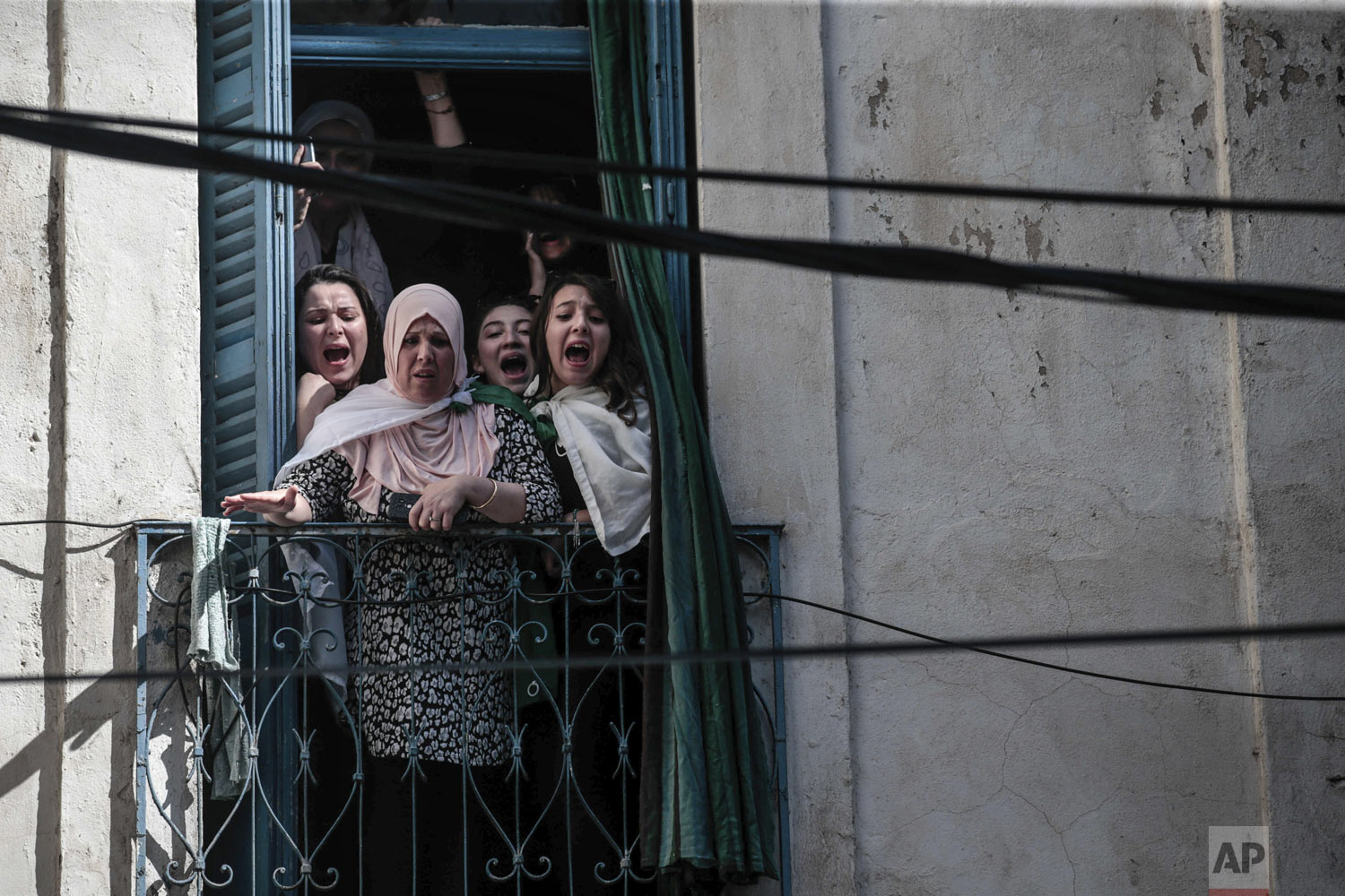 Onlookers react from a balcony as police clash with protesters during a demonstration against the country's leadership, in Algiers, Algeria, on Friday, April 12, 2019. Heavy police deployment and repeated volleys of water cannons and tear gas didn't deter masses of citizens from packing the streets of the capital Friday, insisting that their revolution isn't over just because the president stepped down. (AP Photo/Mosa'ab Elshamy)