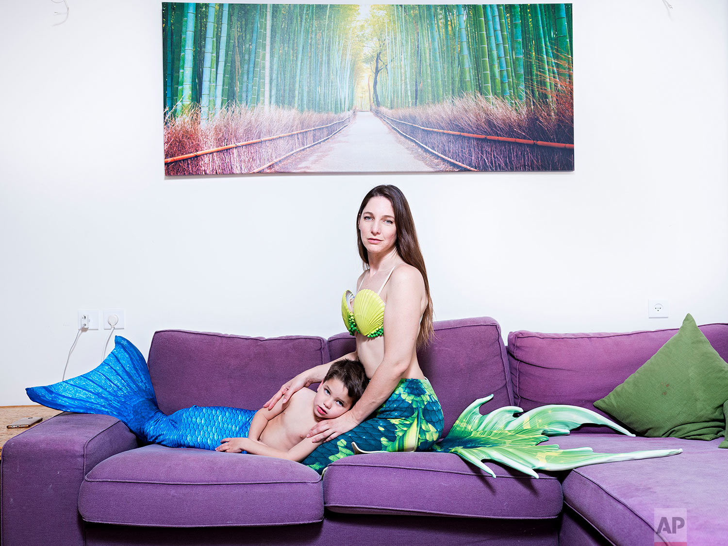 In this Wednesday, Feb. 27, 2019 photo, Shir Katzenell and her son Erez , a member of the Israeli Mermaid Community, poses for a portrait as they wear mermaid tail at their home in Or Akiva, Israel. (AP Photo/Oded Balilty)