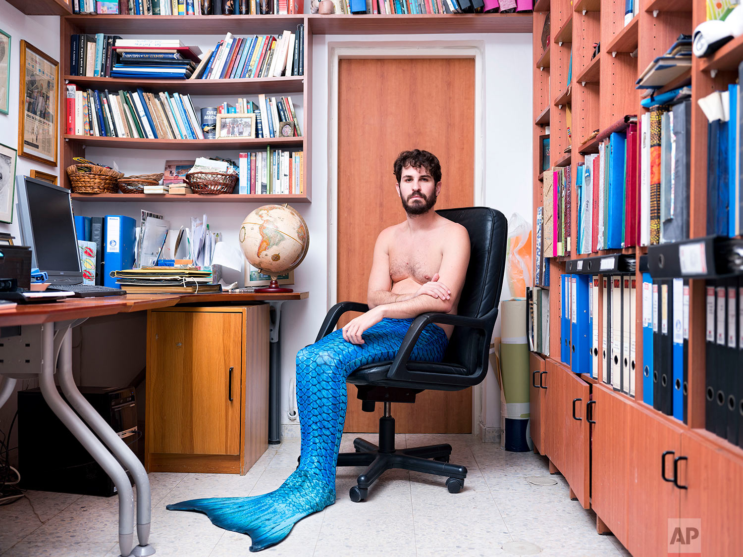 In this Wednesday, Feb. 20, 2019 photo, Yuval Avrami, a member of the Israeli Mermaid Community, poses for a portrait as he wears a mermaid tail at his home in Jerusalem. (AP Photo/Oded Balilty)