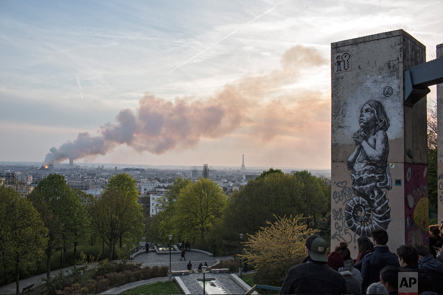 People watch Notre Dame Cathedral burn in Paris, Monday, April 15, 2019. (AP Photo/Rafael Yaghobzadeh)