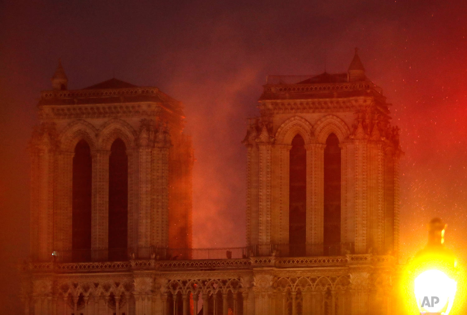 Flames illuminate the night sky as Notre Dame Cathedral burns in Paris, April 15, 2019. (AP Photo/Thibault Camus)