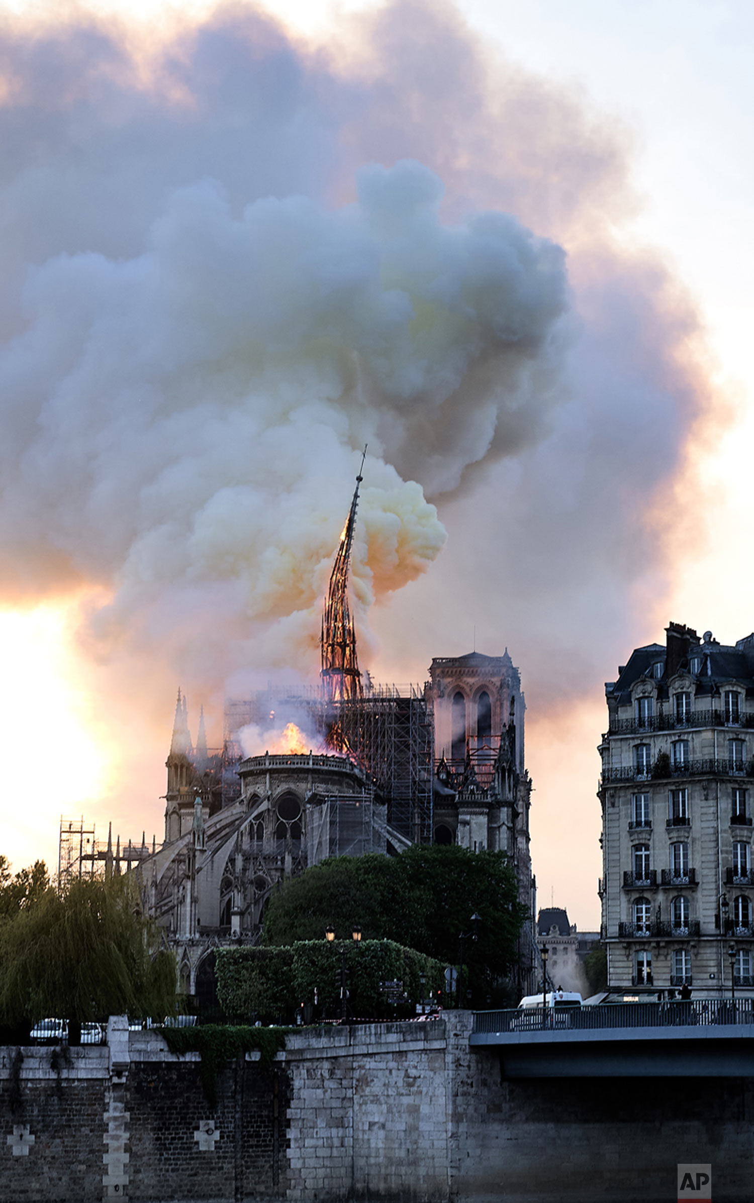 Flames and smoke rise as the spire on Notre Dame Cathedral collapses in Paris, April 15, 2019. (AP Photo/Diana Ayanna)