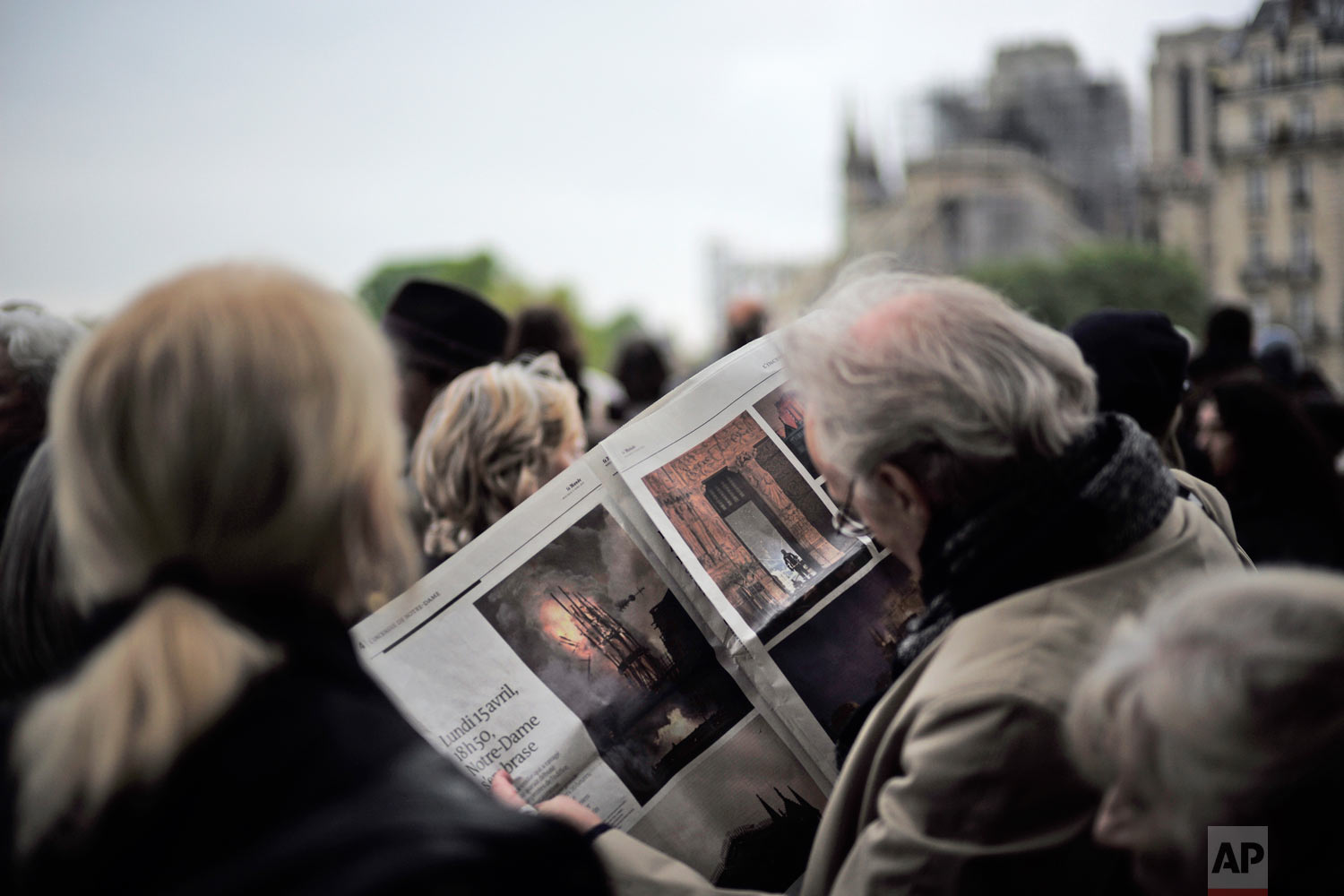 A man looks at pictures of the burning Notre Dame Cathedral in a newspaper as he and others gather near the damaged cathedral, rear, after the fire in Paris, April 16, 2019. (AP Photo/Kamil Zihnioglu)