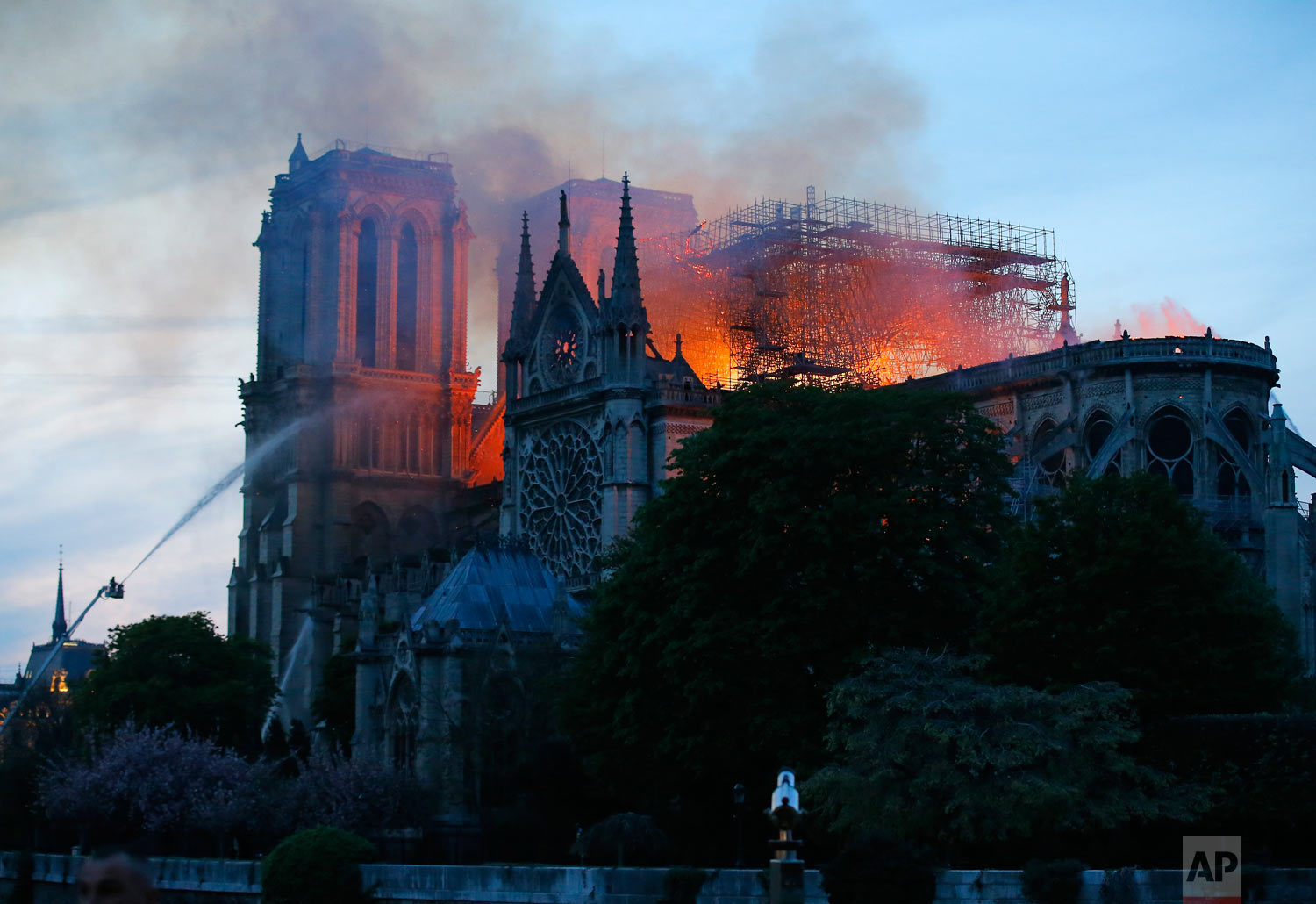 Firefighters tackle the blaze as flames and smoke rise from Notre Dame Cathedral as it burns in Paris, April 15, 2019. (AP Photo/Thibault Camus)