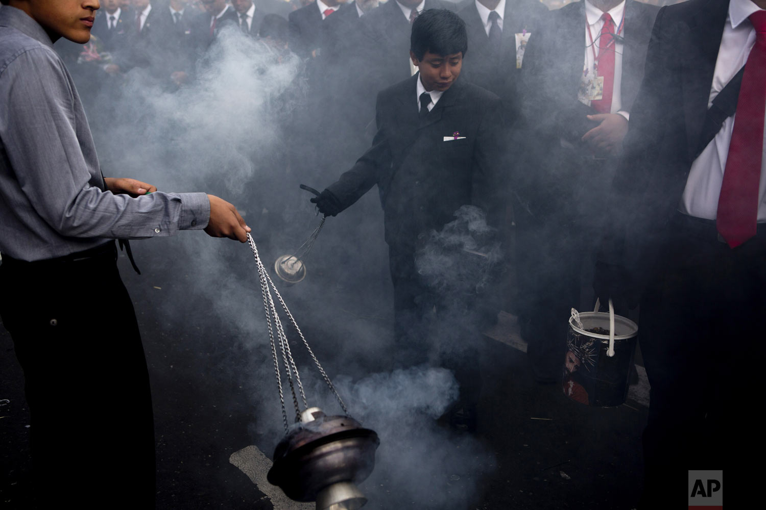 "Boys swing censers using the smoke from incense to purify the path of the Holy Tuesday procession known as ""La Reseña,"" in downtown Guatemala City, Tuesday, April 16, 2019. The Holy Week procession, dating back centuries, parades the La Merced church statues of Jesus of Nazareth and Our Lady of Sorrows as worshippers throw bouquets of flowers onto the platforms. (AP Photo/Moises Castillo)"