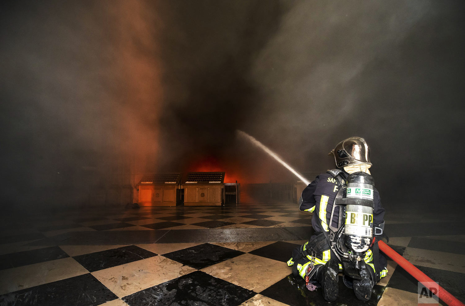 "In this photo provided by the Paris Fire Brigade, firefighters spray water inside the Notre Dame cathedral, Monday April 15, 2019. An inferno that raged through the historic site for more than 12 hours destroyed its spire and its roof but spared its twin medieval bell towers, and a frantic rescue effort saved the monument's ""most precious treasures,"" including the Crown of Thorns purportedly worn by Jesus, officials said Tuesday. (Benoit Moser/BSPP via AP)"