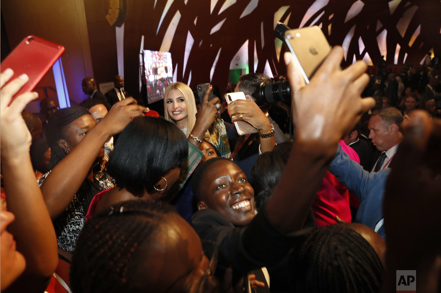 People crowd around U.S. White House senior adviser Ivanka Trump, back left, to take selfies with her at the end of the Women Entrepreneurs Finance Initative, or We-Fi, event sponsored by the World Bank Group, Wednesday, April 17, 2019, in Abidjan, Ivory Coast. Ivanka Trump is promoting a White House global economic program for women. (AP Photo/Jacquelyn Martin)